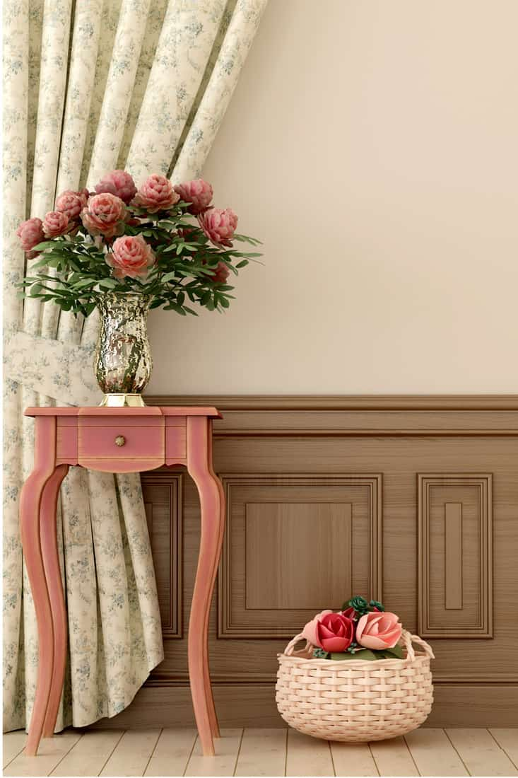 Beige colored wall with flower vase on top of a peach colored wooden drawer complementing a long, beige and grey floral tied-back curtain