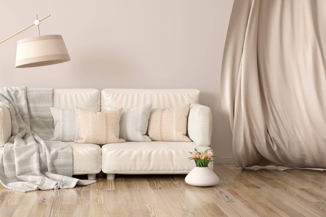 Beige wall with off-white sofa, matching pillows and grey striped blanket placed on top