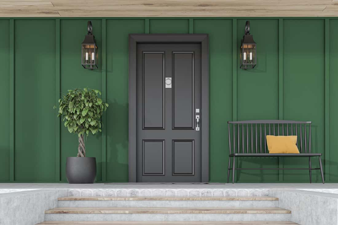 Black door with dark green colored walls and wall lamps on each side