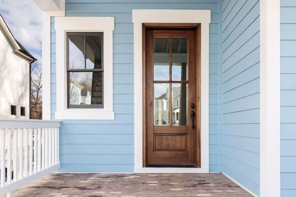 Blue front porch with brown door with white framing