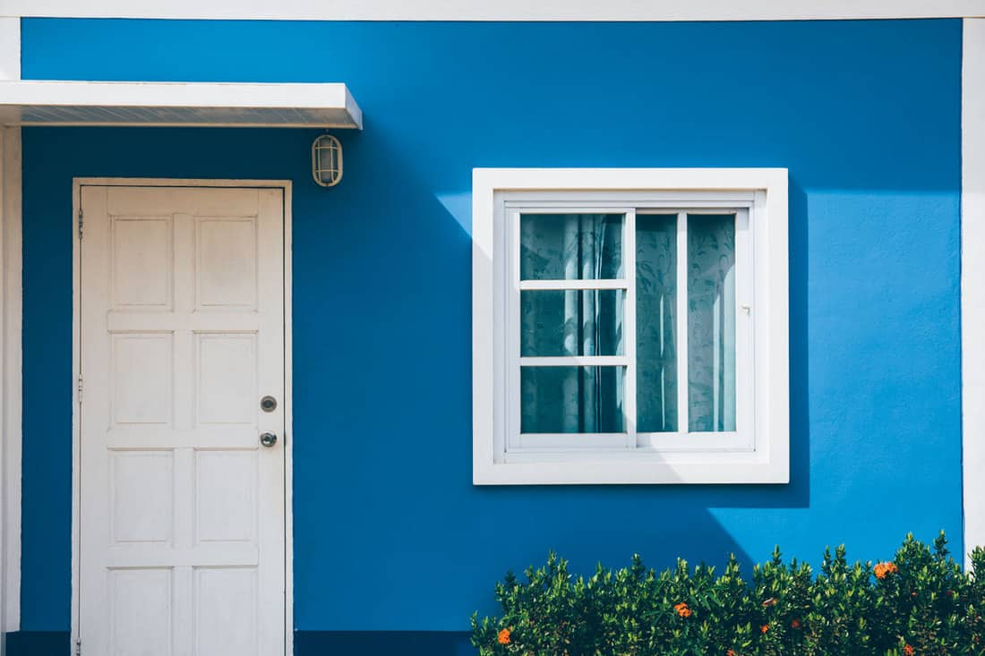 Blue front porch with white door and small windows