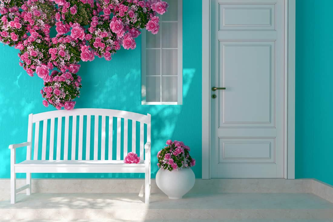 Blue walled front porch with white chair and pink hanging flowers