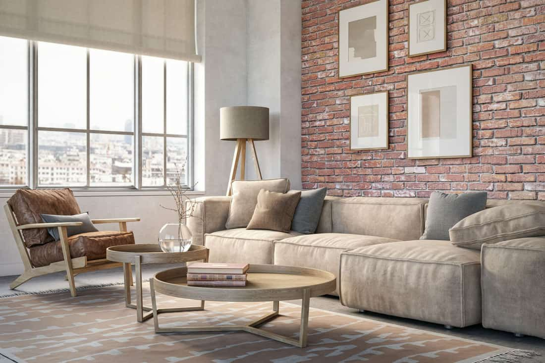 Brick walled living room with brown sofa near huge windows