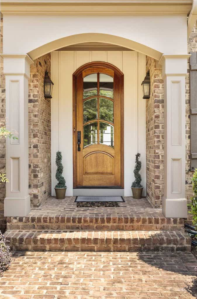 Brown front door entrance to an upscale home with white architectural features