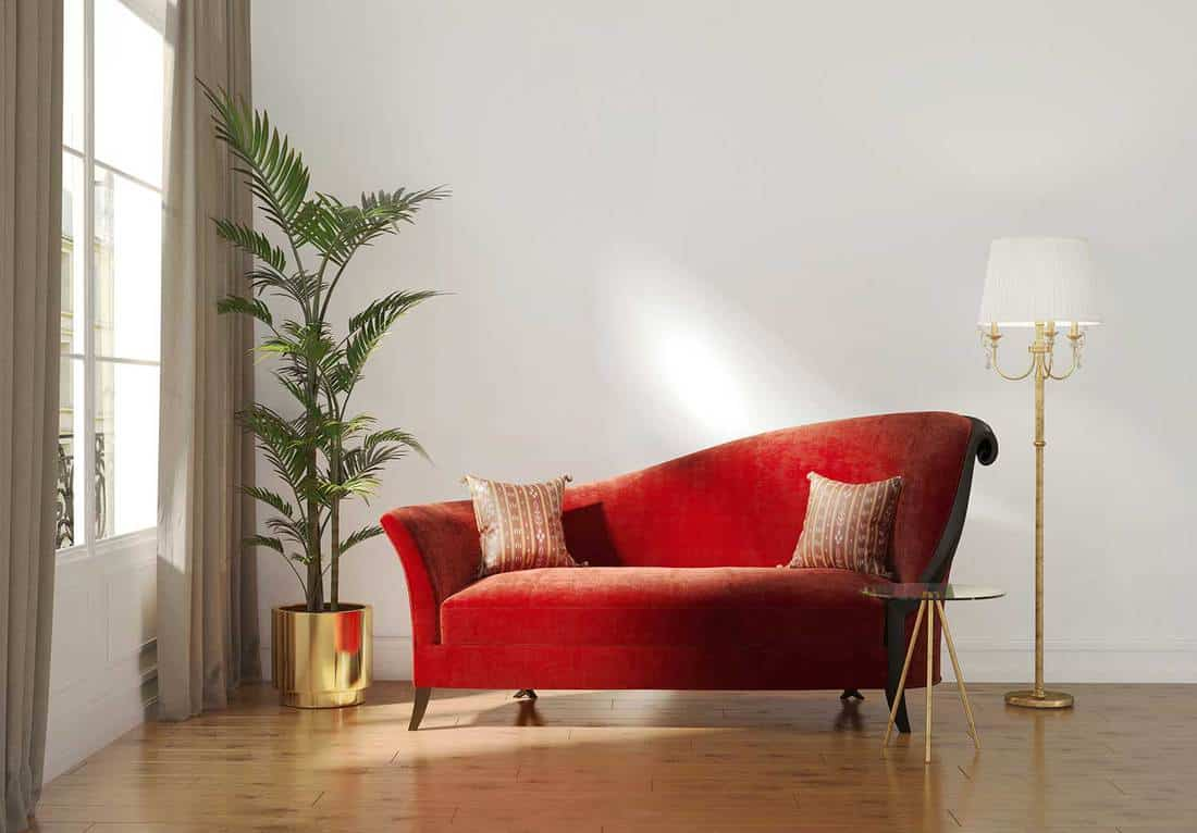 Classic Parisian luxury interior with red chaise lounge and gold floor lamp