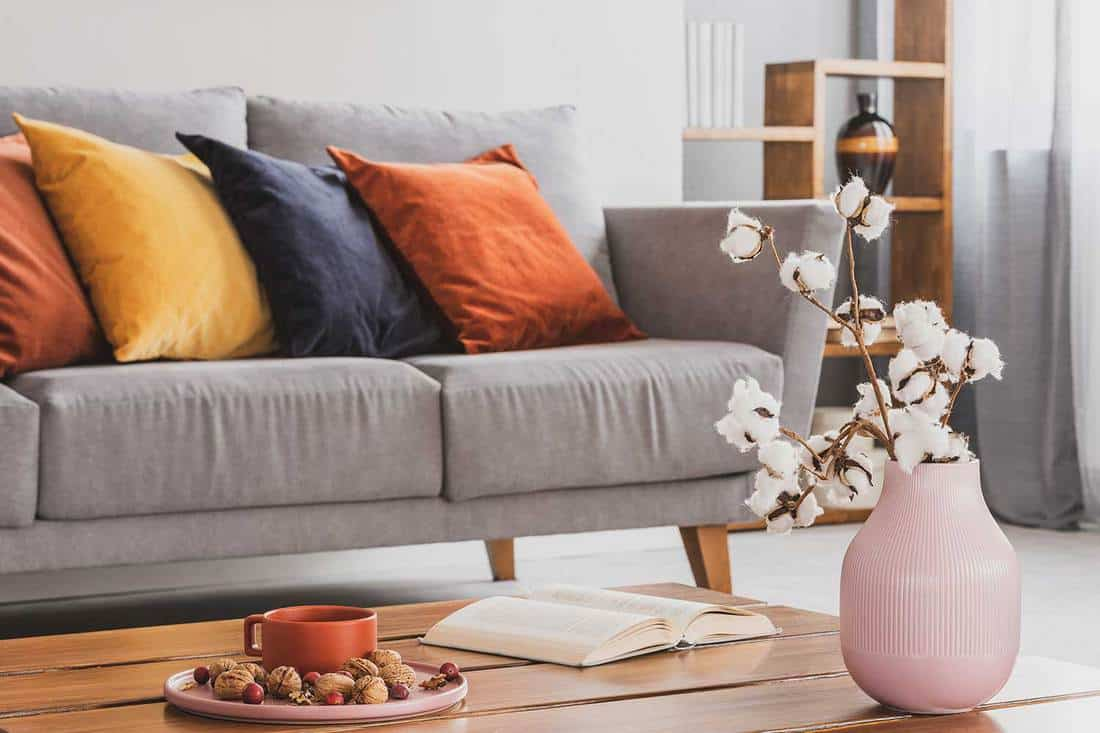 Closeup of elegant wooden coffee table in trendy living room interior with grey sofa with pillows