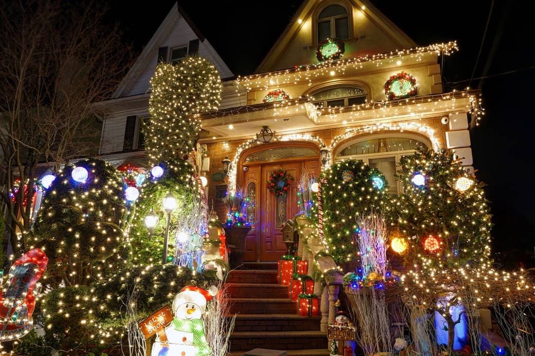 Colonial house covered with Christmas lighting wreath and Santa at the staircase
