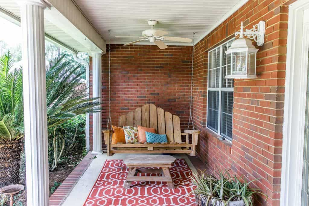 Colorful and modern bohemian boho outdoor front porch decoration with seating and a plant. The house is red brick and traditional.