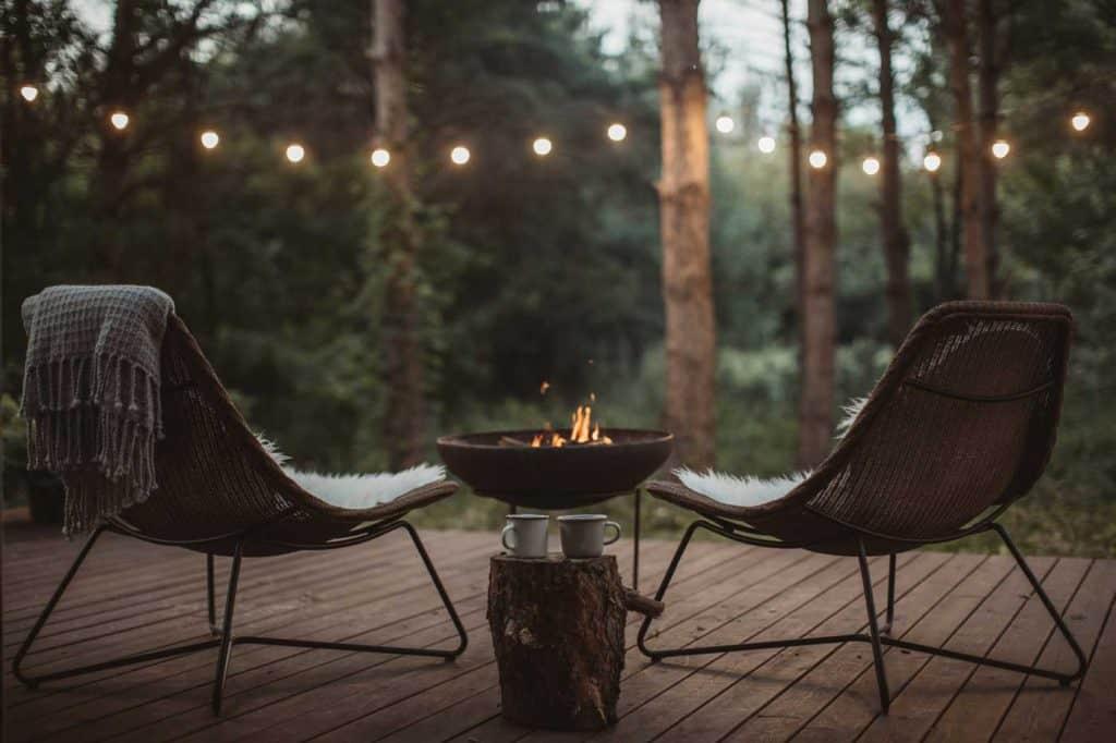 Przedni ganek domku z dwoma przytulnymi krzesłami i kominkiem. Koce i filiżanki do kawy czekają na kogoś, kto będzie się nimi delektował.