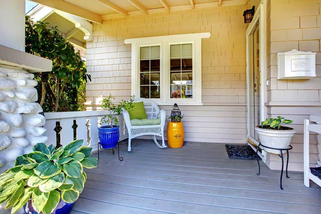 Covered entrance porch with plants and chair