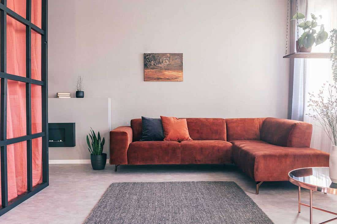 Cozy living room interior with corner sofa with pillows and painting on the wall