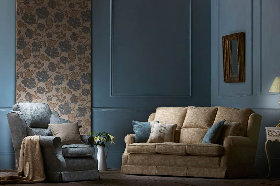 Dark blue walled living room with brown sofa and blue accent chair on the side