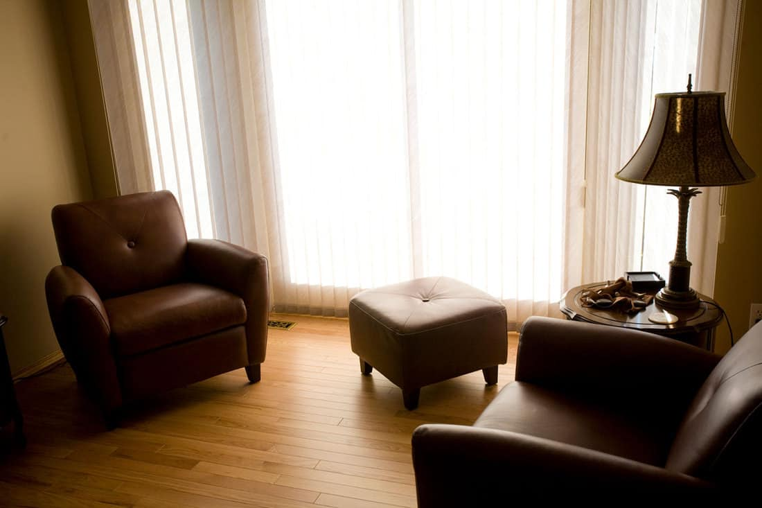 Dark living room with two dark chairs with lamp on the side and closed curtains
