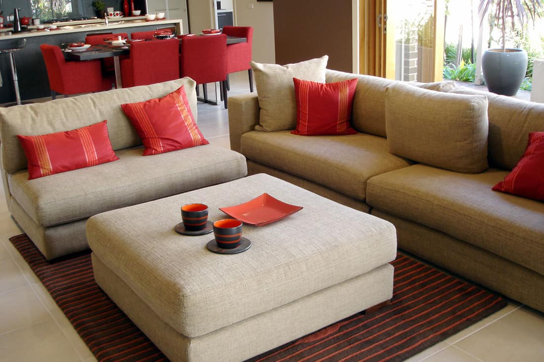 Dirty white colored sofa with red pillows