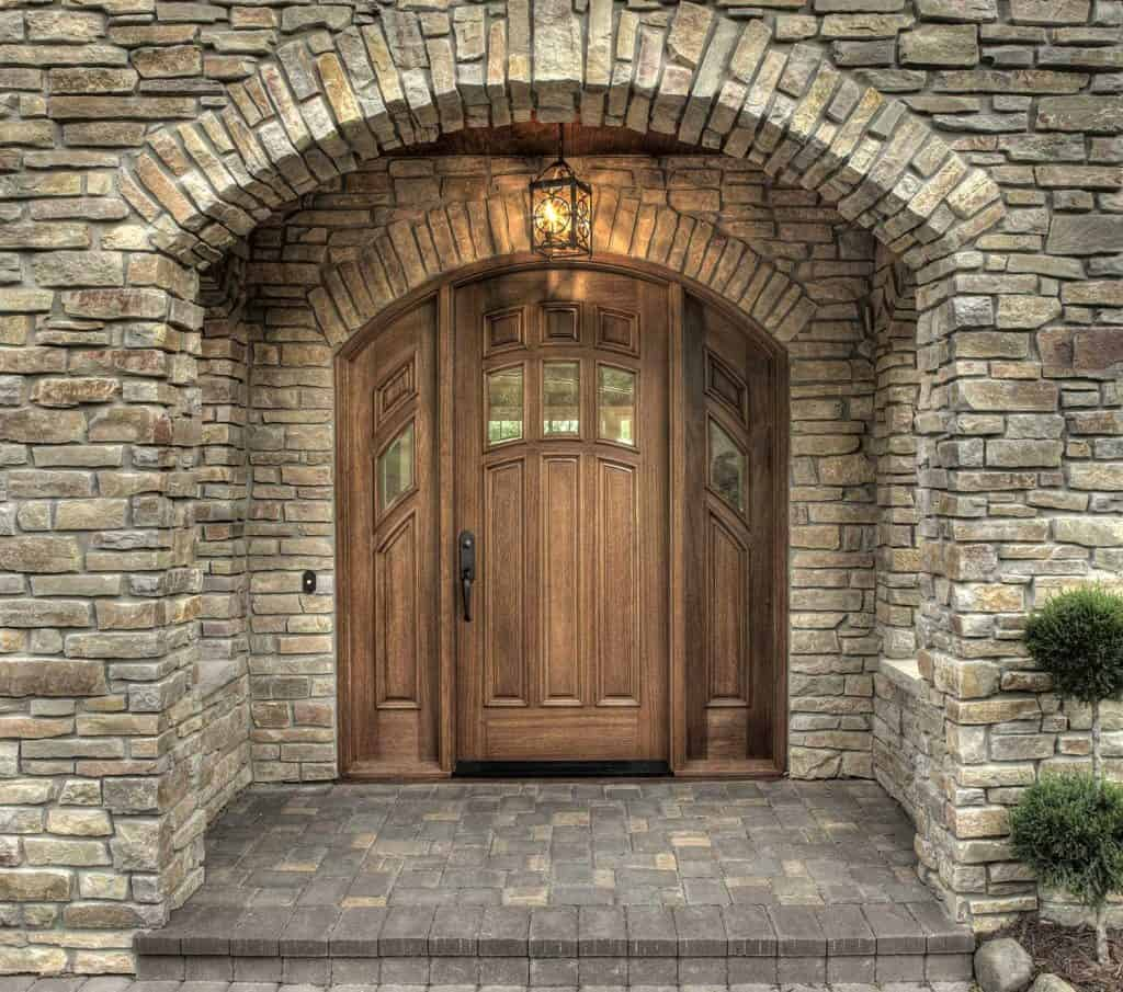 Dramatic stone entry with arched custom wooden door