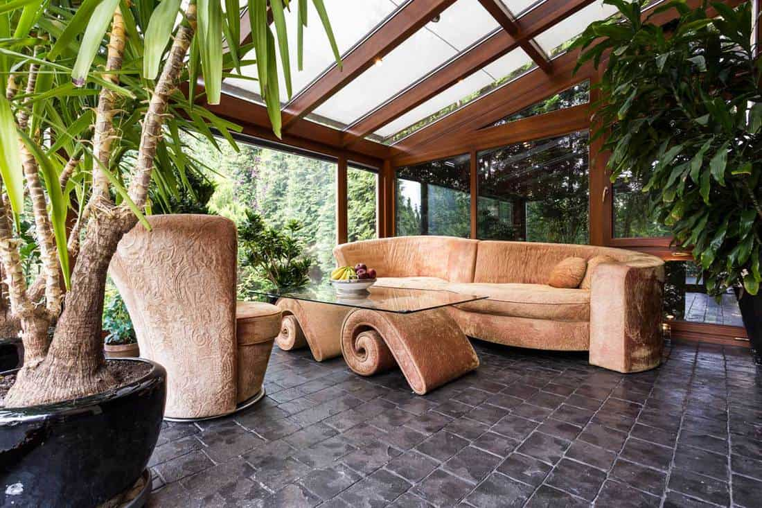 Entertainment room with long couch, indoor plants, and clear panel roofing