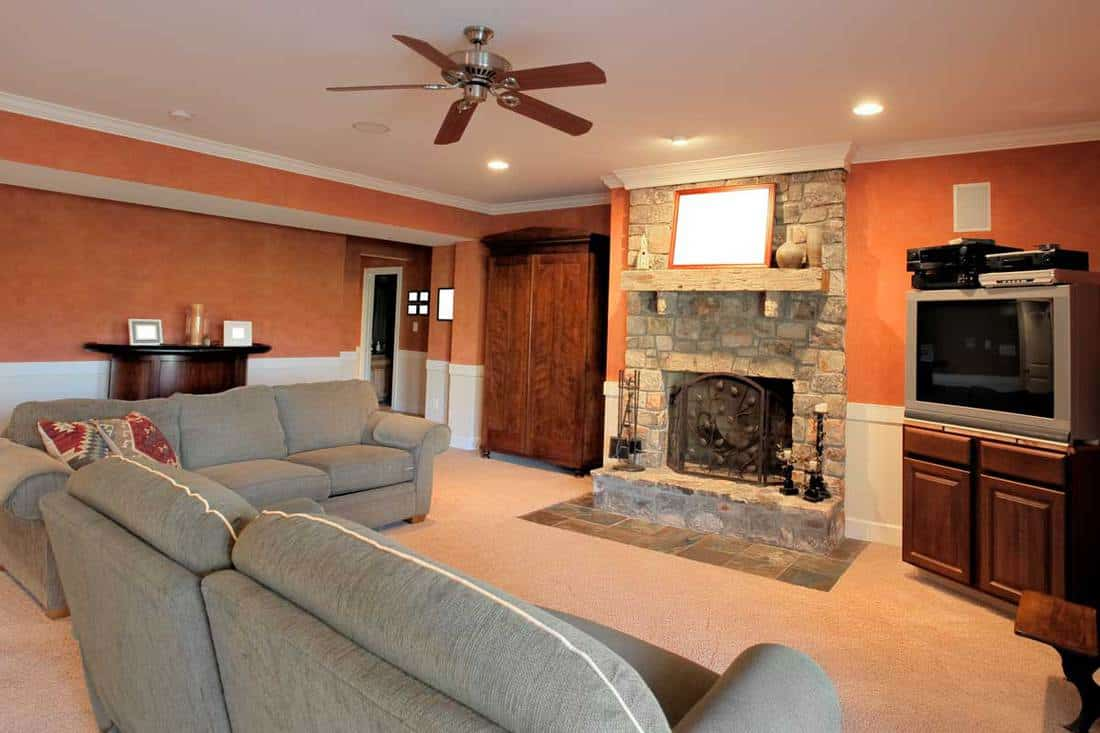 Family Room Interior with grey sofas near a brick fireplace