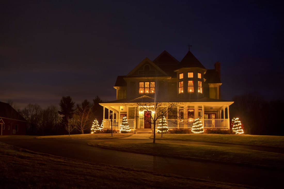 Farmhouse covered with Christmas lights at the porch
