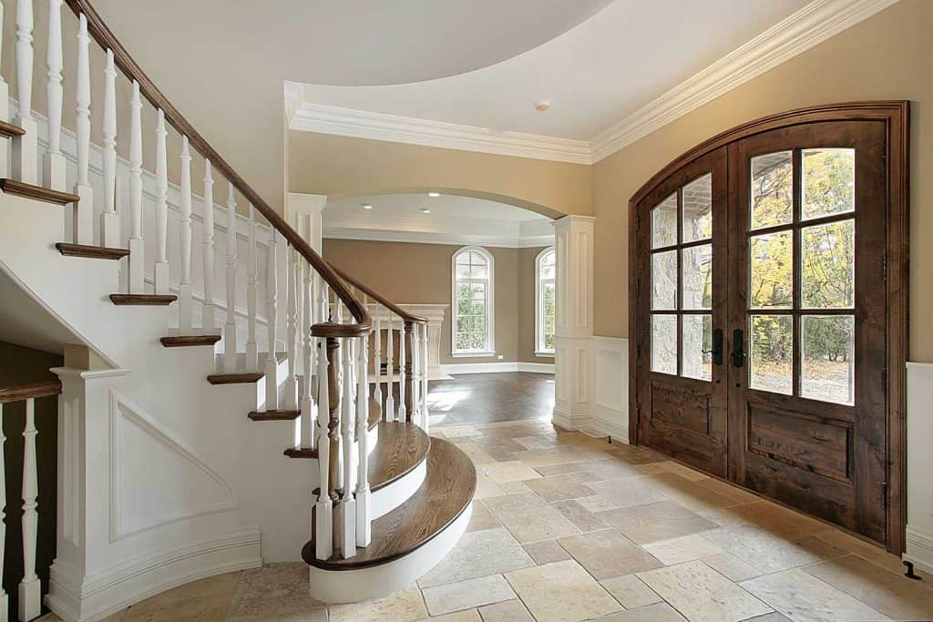Foyer in new construction home with rustic arched front door