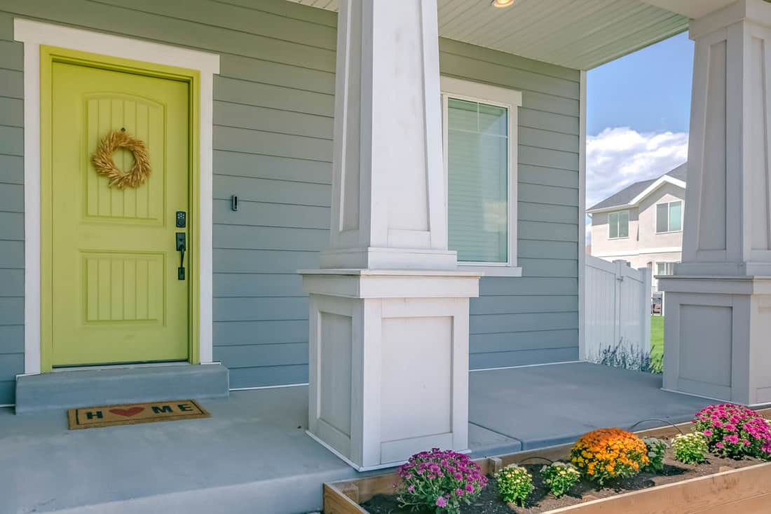 Front porch colored with blue and a light yellow color with wreath