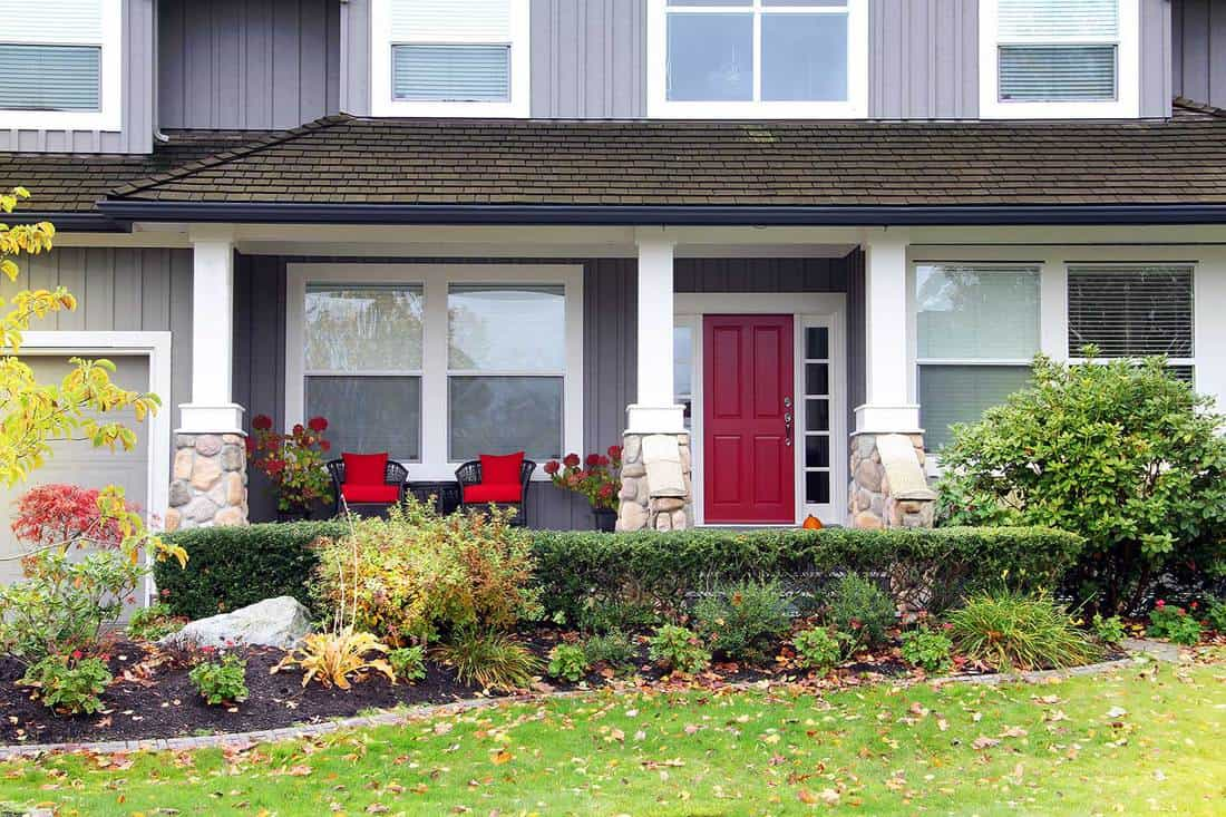 Front porch of a beautiful Canadian house with red chairs and red door