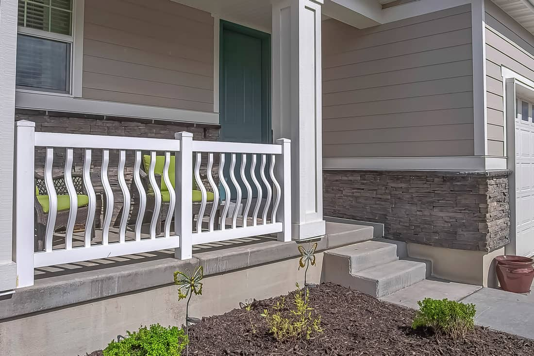 Front porch of a gray colored house and small garden on front