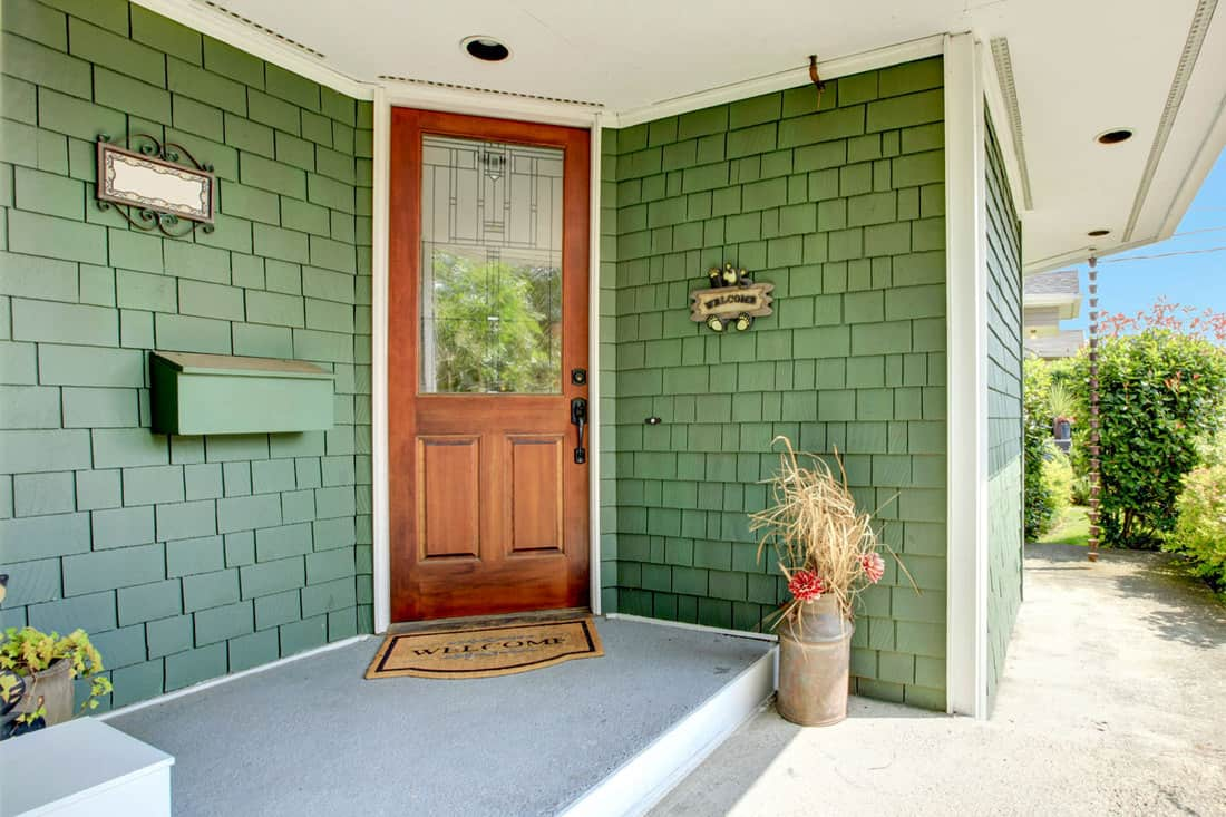 Front porch of a house with a brown wooden door and green colored brick wall