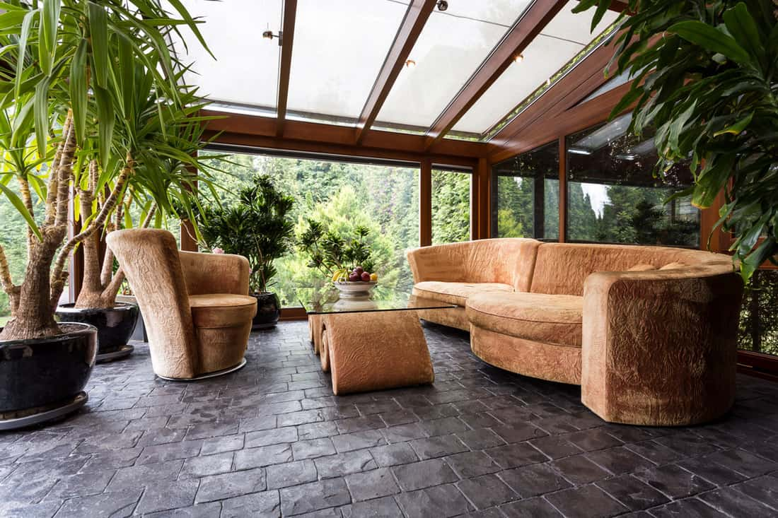 Front porch of a house with curved sofas and weird looking table