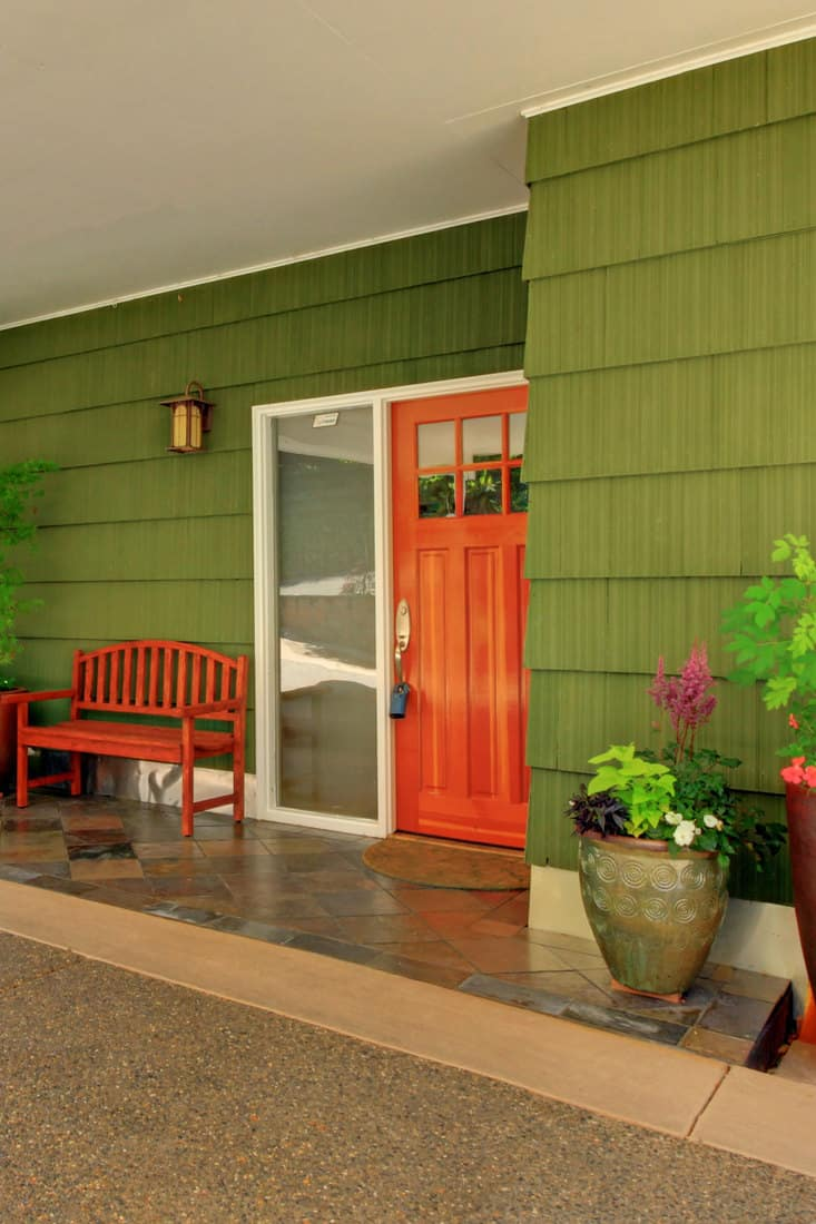 Front porch of a house with green walls, brown door with glass window on the side