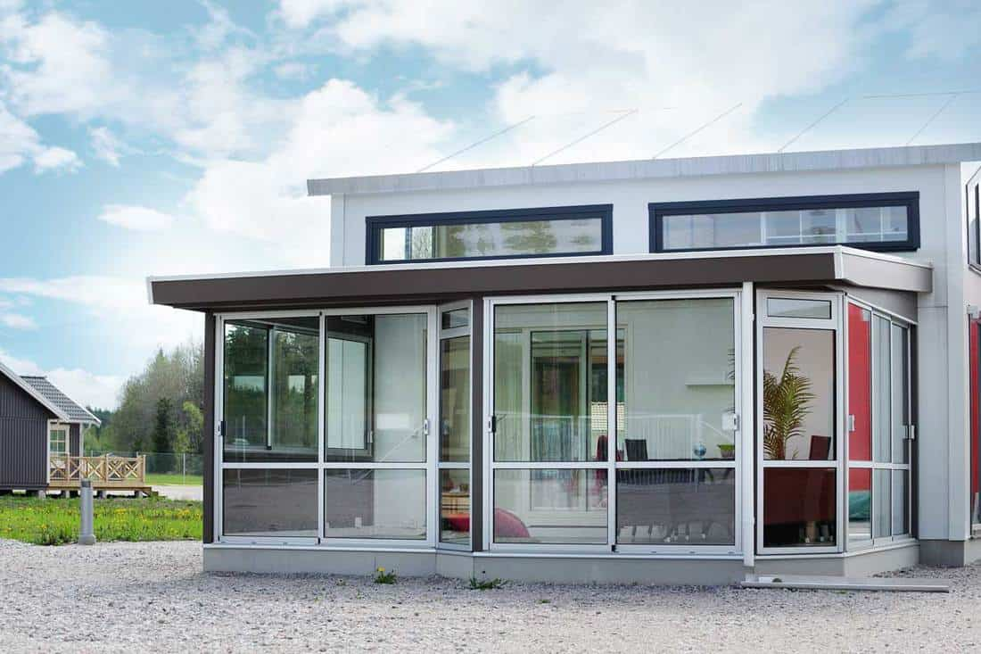 Front porch of a modern house with seamless glass walls