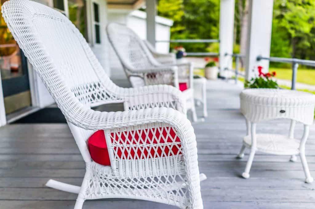 Przedni ganek domu z białymi fotelami bujanymi na drewnianym pokładzie