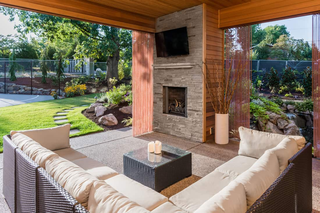 Front porch with fire place and rectangular sofa facing the fireplace