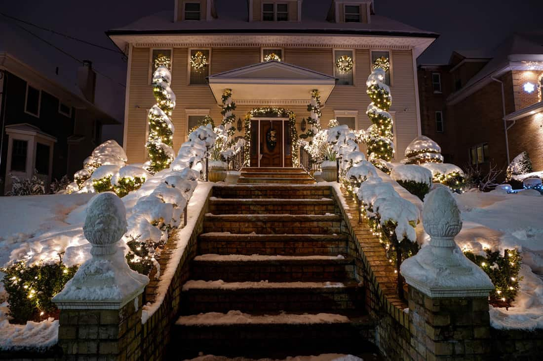 Front yard of a house with a staircase decorated with Christmas light up to the porch