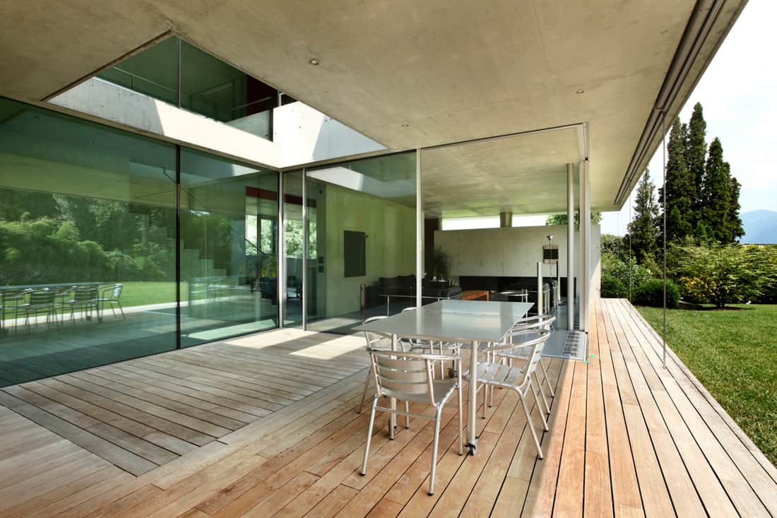 Glass covered front porch with wooden decking and steel chairs