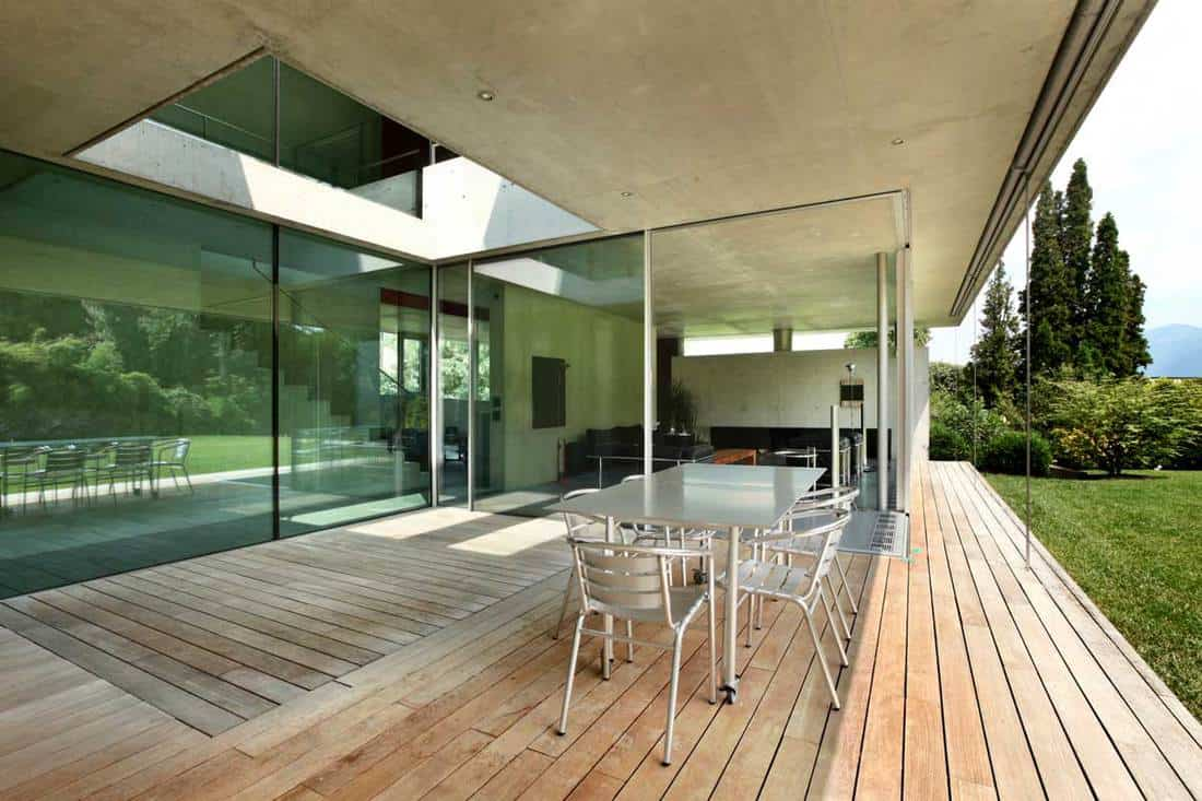 Glass enclosed porch of a modern house with chairs positioned outside