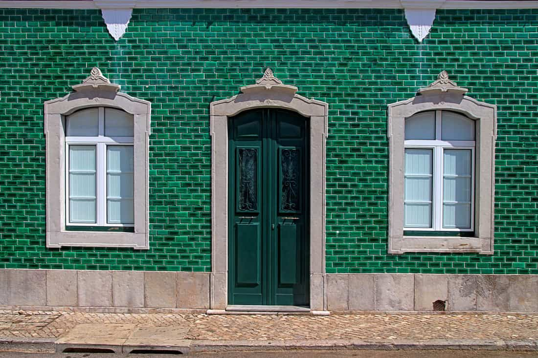 Green colored brick wall with a matching green door