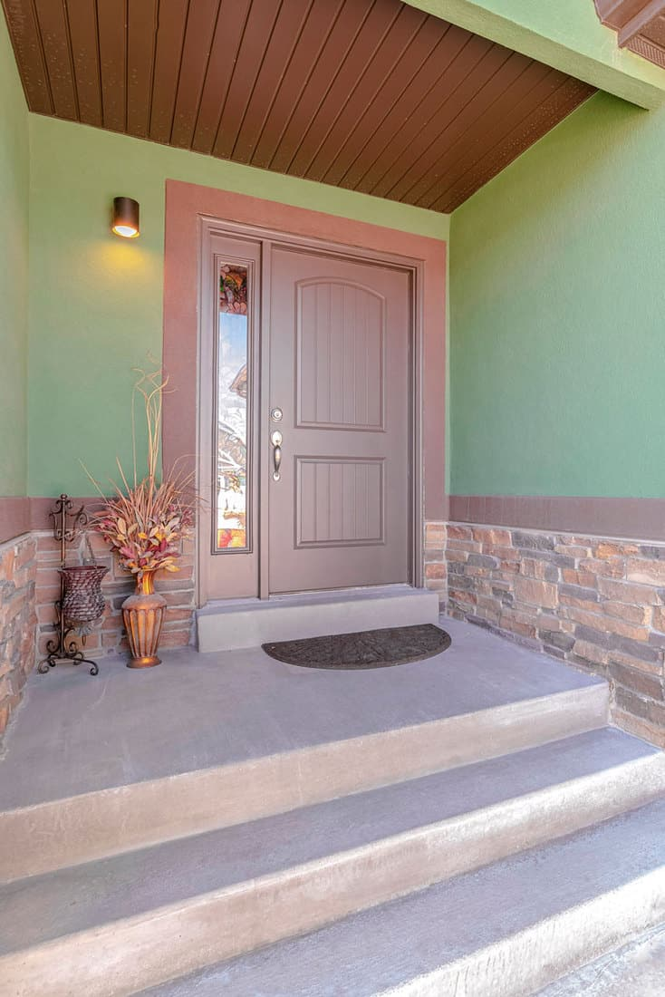 Green colored walls with brown door and wall lamp on the side