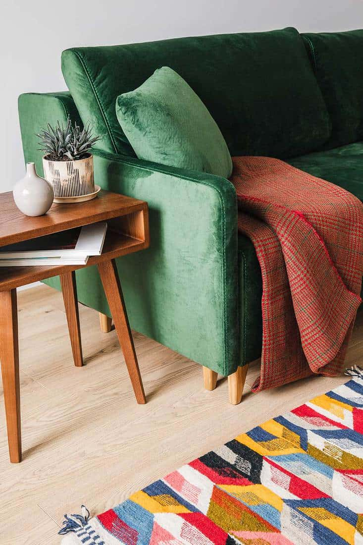 Green sofa with pillow and blanket near coffee table