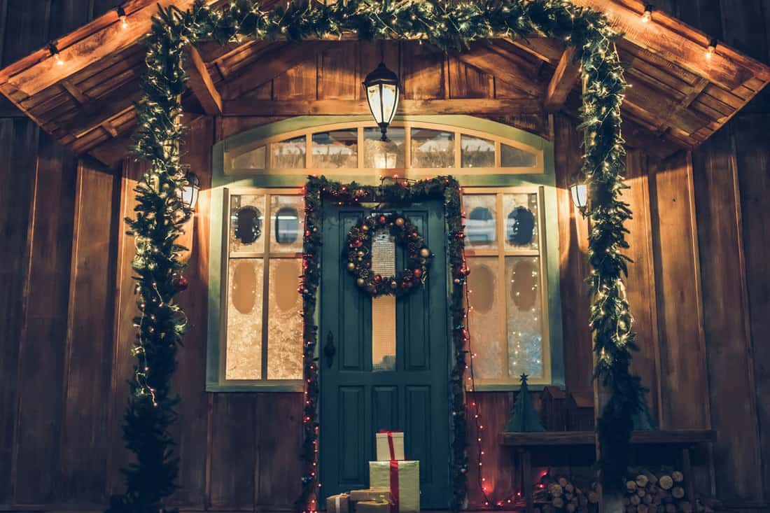 House with Christmas decoration, lighting, and wreath a the door