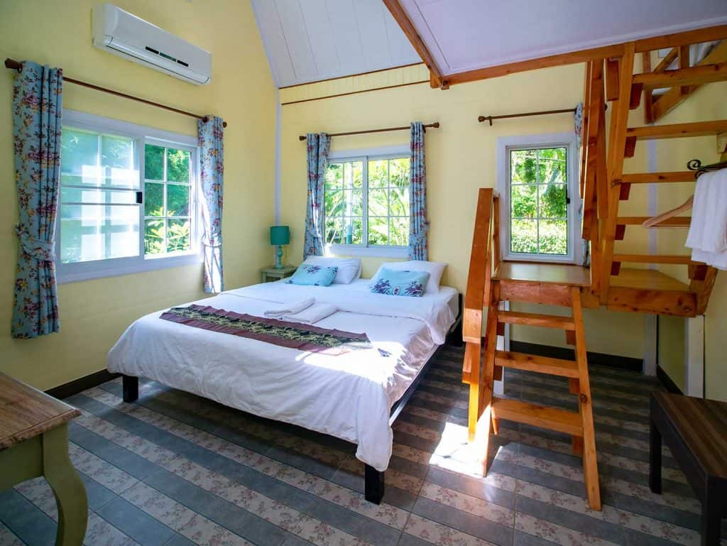 Interior of hotel resort with bed and wooden ladder to mezzanine