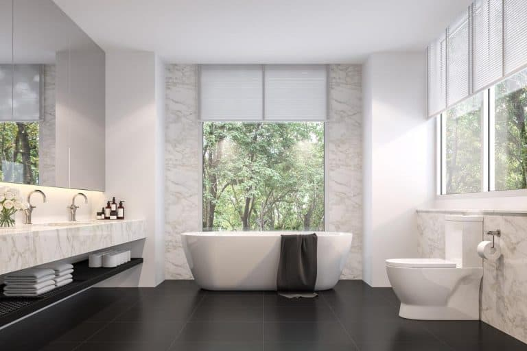 Luxurious bathroom with white walls, white bathtub, and dark tiled flooring, What is the Best Color For the Bathroom Floor?