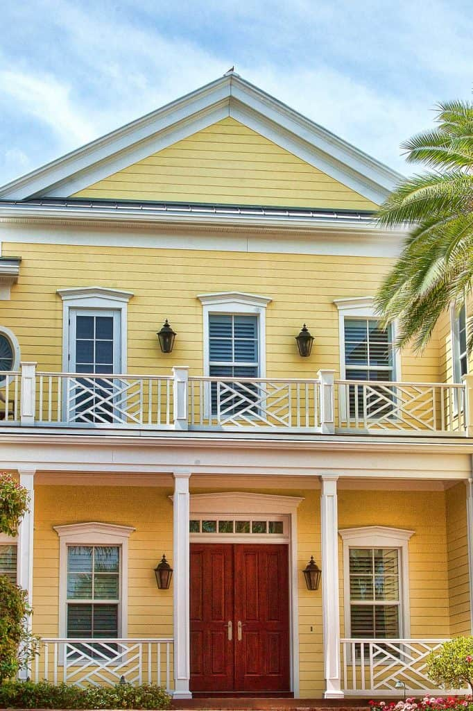 Luxury elegant new yellow beach home with yellow exterior and brownish double door in Venice, Florida
