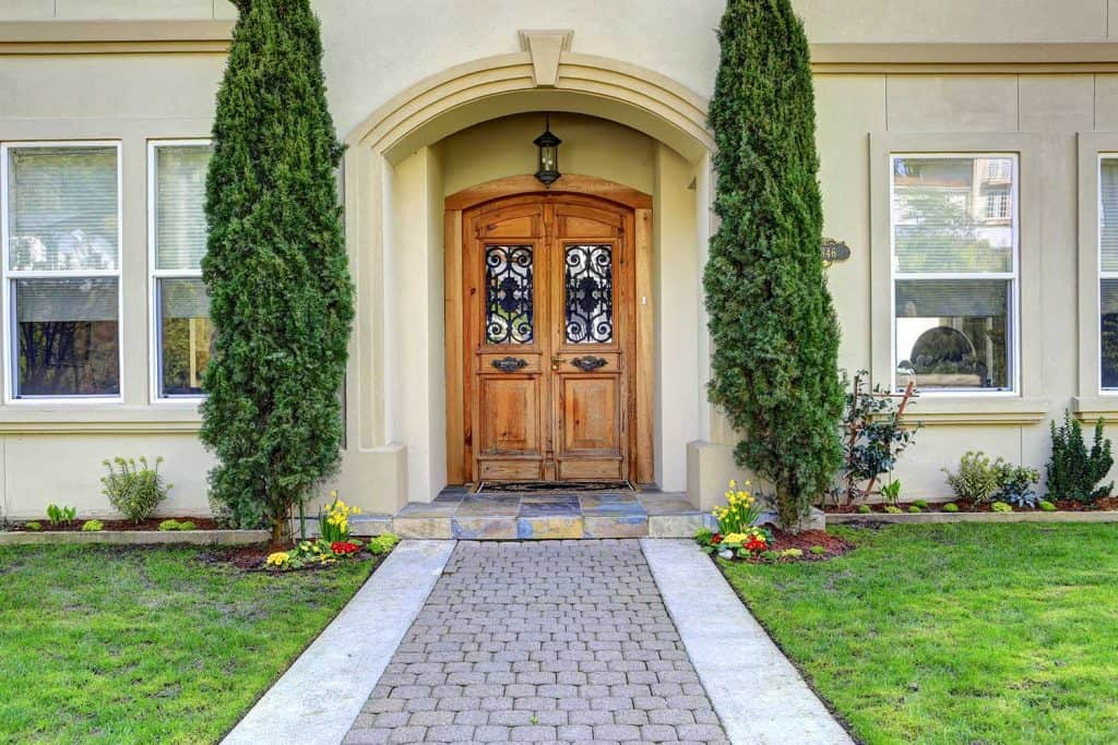 Luxury house entrance porch with walkway and arched wooden front door