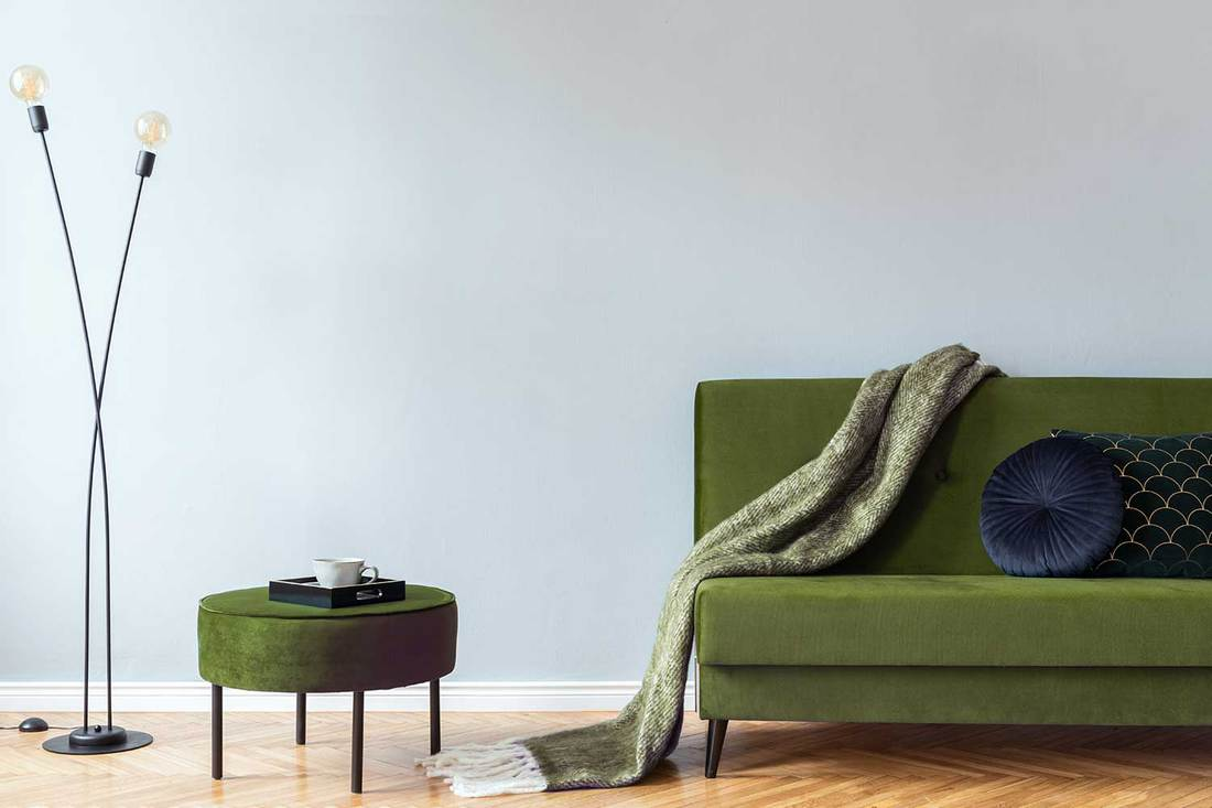 Minimalistic home interior with green velvet design sofa and pouf, lamp, elegant blanket and pillows