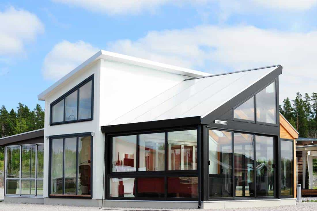 Modern black and white colored house with overall glass walls