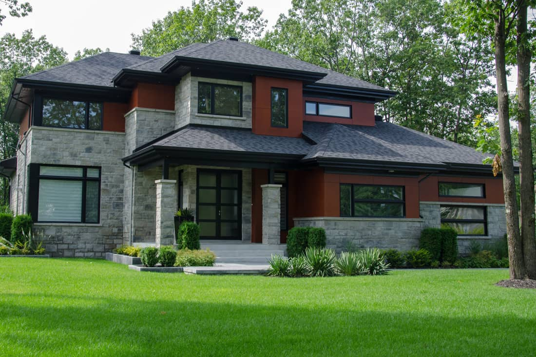 Modern house with black framed windows, stone cladding combined with brown colored walls