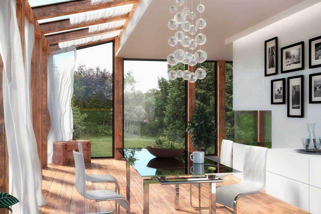 Modern living room with glass walls with wooden post and clear roof panels for lighting