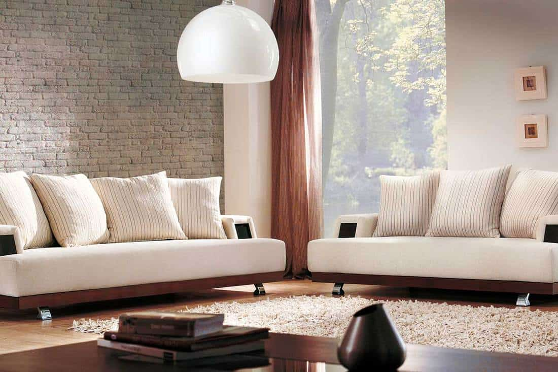 Modern living room with off-white couches, off-white striped throw pillows and area rug