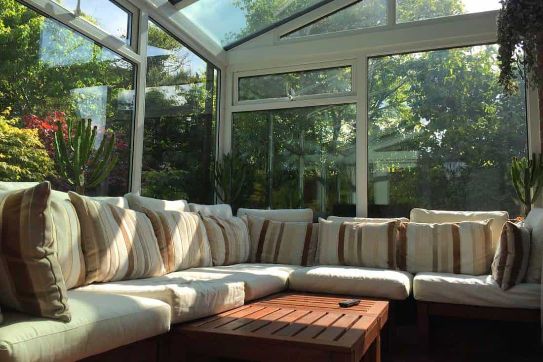 Nature themed living room with white sofas and glass walls