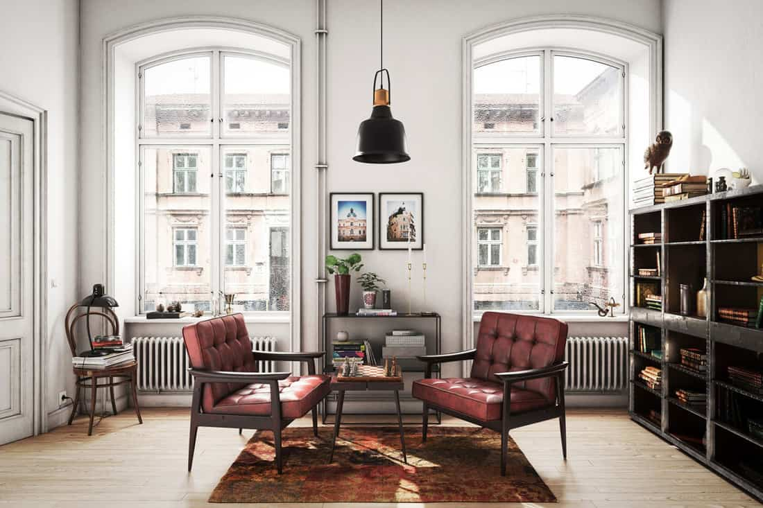 Old fashioned living room with old styled chairs with two arched windows at the background